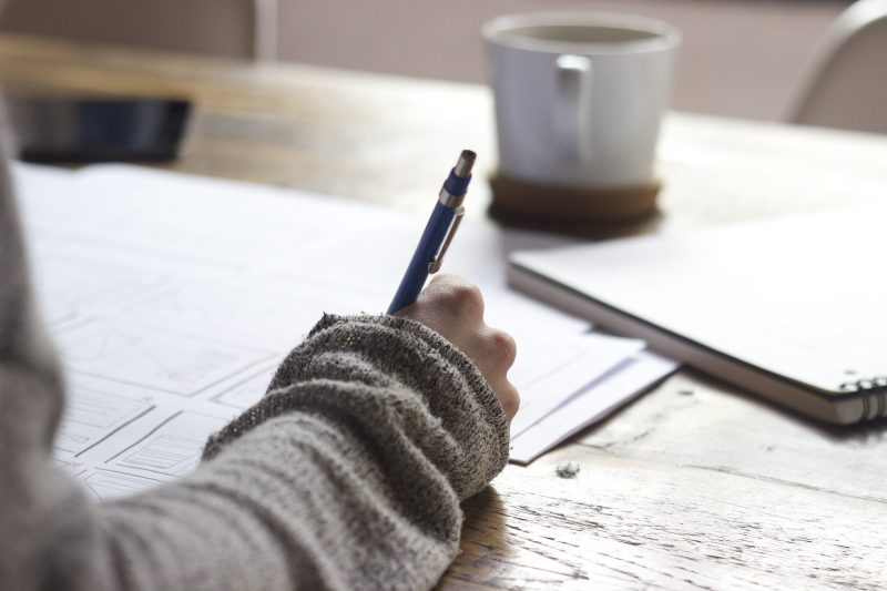 A hand writing an article